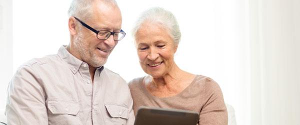 Couple d'aînés canadiens à la maison avec une tablette, cherchant à en savoir plus sur les hypothèques inversées
