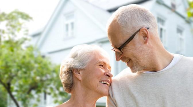Couple de personnes âgées canadiennes debout devant leur maison et songeant à prendre un prêt sur valeur domiciliaire.