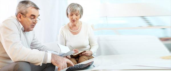 Un couple d'aînés canadiens utilisant la calculatrice d'hypothèque inversée pour calculer le montant du prêt qu'ils recevront en fonction de la valeur nette de leur résidence.
