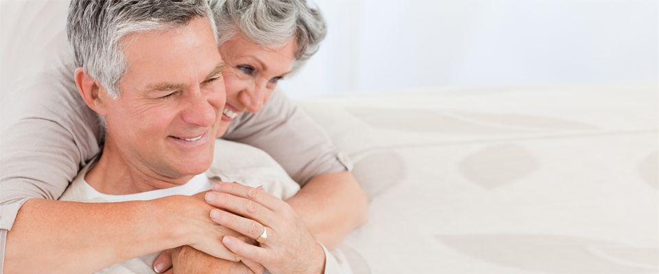 Couple d'aînés s'enlaçant et souriant alors qu'on répond à leurs questions sur les hypothèques inversées de la Banque HomeEquity, Canada.