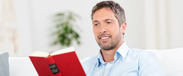 Homme confortablement assis et lisant un livre dans une maison, heureux de la sécurité offerte par l'hypothèque inversée canadienne pour laquelle ses aînés avaient opté.